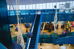 Shopping mall at christmas. Time with gold and blue ornaments and people walking around and riding the escalator on a busy day stock photography