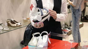 Shopping in the mall. Close up woman's hands holding and twisting a shoe in the shop stock footage