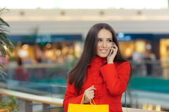 Shopping Mall Girl in a Red Coat Talking on Smartphone. Smiling woman with shopping bags in a mall talking on the phone Stock Photo