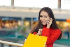 Shopping Mall Girl in a Red Coat Talking on Smartphone. Smiling woman with shopping bags in a mall talking on the phone Stock Photography