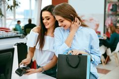 Shopping Mall. Girls Paying With Credit Card. Shopping Mall. Beautiful Girls In Stylish Clothes Paying With Credit Card At Store Checkout. High Resolution Stock Image