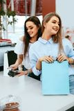 Shopping Mall. Girls Paying With Credit Card. Shopping Mall. Beautiful Girls In Stylish Clothes Paying With Credit Card At Store Checkout. High Resolution Royalty Free Stock Image