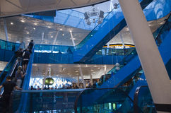 Shopping mall interior. Modern shopping mall with bright interior, white furniture and blue details, glass windows and people riding an escalator stock image