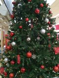 Large green Christmas tree with bright coloured decorations. In a shopping mall with lights and baubles Stock Photography