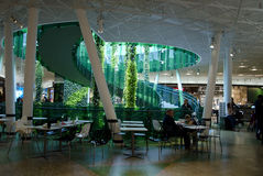 Shopping mall lounge. Shopping mall interior with lounge area and green large plants, tables and chairs, a man and a boy resting stock images