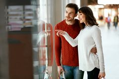 Shopping Mall. Man And Woman Looking Through Store Window. Shopping Mall. Happy Man And Beautiful Woman Smiling And Looking Through Store Window. High Resolution Royalty Free Stock Images