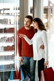 Shopping Mall. Man And Woman Looking Through Store Window. Shopping Mall. Happy Man And Beautiful Woman Smiling And Looking Through Store Window. High Resolution Stock Photo