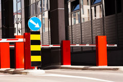 Shopping mall parking entrance. Mandatory way sign and parking barrier, building in background Stock Photos