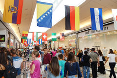 Shopping Mall People Flags. Aprilia, Italy - July 2014: People walking and shopping in a shopping Italian mall full of international flags Stock Photos
