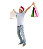 Shopping man in christmas hat keeping bags Stock Photo