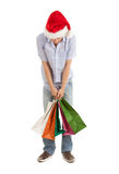 Shopping man in christmas hat keeping bags Stock Images