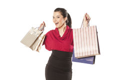 Shopping Mania. Happy and smiling blue-eyed brunette holding shopping bags on white background Royalty Free Stock Images