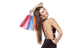 Shopping mania. Pretty young woman in short black dress posing with shopping bags Royalty Free Stock Images