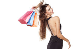 Shopping mania. Pretty young woman in short black dress posing with shopping bags Royalty Free Stock Photo