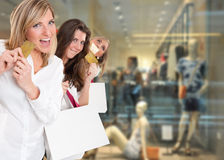 Shopping mania. Three cute girls holding credit cards at the mall Royalty Free Stock Photos