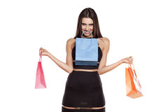 Shopping mania. Woman posing with shopping bags in her hands and teeth Royalty Free Stock Photo