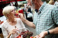 Shopping, mat, försäljning, consumerism och folkbegrepp - lyckligt högt par som köper ny mat arkivfoto