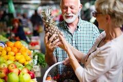 Shopping, mat, försäljning, consumerism och folkbegrepp - lyckligt högt par som köper ny mat royaltyfria bilder