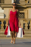 Shopping In The Med. A classically beautiful Mediterranean woman walking through a European city clutching full shopping bags and smiling an enigmatic smile Stock Images