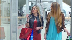 Shopping: meeting friends. two girls .slow motion. Two girls meet at his girlfriend shopping, show off to each other things stock video