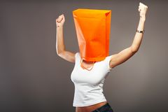 Shopping metaphor. Woman with shopping bag over her head Stock Photos