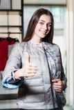 Shopping, mode, stil, sälja, shopping, affär och folk Härlig lycklig ung kvinna för begrepp som visar grupp i kläder royaltyfria foton