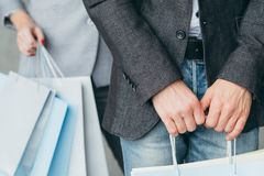Shopping money spending addiction bags hands. Shopping and money spending addiction. cropped shot of men and women with multiple bags in hands royalty free stock images