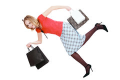 Shopping mood. Pretty blonde girl running with shopping bags in hands Stock Photo