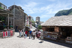 Shopping in Mostar. MOSTAR, BOSNIA AND HERZEGOVINA - MAY 18, 2013: Tourists look at the souvenir shops and local crafts in Mostar. On May 18, 2013 in Mostar Royalty Free Stock Image