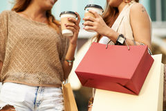 Shopping obsession. Cropped image of female shopaholics chatting and drinking coffee royalty free stock photos