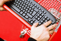 Shopping online. Concept: hands pushing shopping cart and computer keyboard, e commerce Stock Images