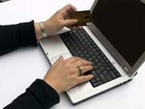 Shopping online. Shopping over the Internet, female hands holding credit card and typing order on a laptop keyboard Royalty Free Stock Images