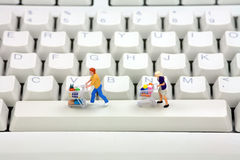 Shopping online concept. Miniature shoppers with shopping carts on a computer keyboard. Online shopping concept Royalty Free Stock Photo