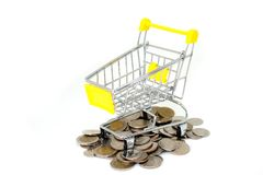 Empty yellow mini shopping cart or supermarket trolley with pile of silver money coins. Shopping Online Concept : Empty yellow mini shopping cart or supermarket Royalty Free Stock Photography