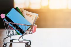 Shopping online at home with credit card in shopping cart model on wooden table. Debt and payment concept Royalty Free Stock Images