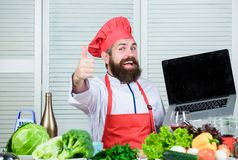 Shopping online. Man chef searching online ingredients cooking food. Grocery shop online. Delivery service. Chef laptop. At kitchen. Culinary school. Hipster in royalty free stock image