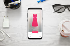 Shopping online with a mobile phone. Woman choose size and color of dress with store app. Top view of mobile and desk Stock Photography