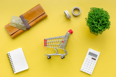 Shopping in online store. Bank card nearby purse, calculator and shopping cart on yellow background top view Stock Photo