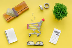 Shopping in online store. Bank card nearby purse, calculator and shopping cart on yellow background top view Stock Photography
