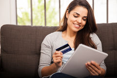 Shopping online with a tablet. Cute young woman shopping online with her credit card and a tablet computer at home Stock Images