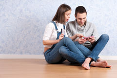 Shopping online together. Beautiful young loving couple shopping online while sitting on the floor together stock image