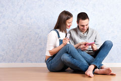 Shopping online together. Beautiful young loving couple shopping online while sitting on the floor together royalty free stock photo