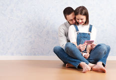 Shopping online together. Beautiful young loving couple shopping online while sitting on the floor together royalty free stock photos