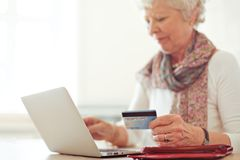 Shopping Online Using a Credit Card. Grandmother using a credit card to make an online transaction Royalty Free Stock Images