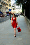 Shopping on a Paris street. A young woman walking along a street in Paris with a shopping bag stock photo