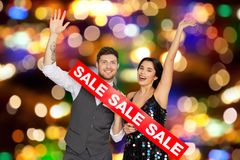 Happy couple with red sale sign. Shopping, people and fashion concept - happy couple with red sale sign over holidays lights background Stock Photography