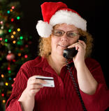 Shopping by phone. A grandma ordering holiday gifts over phone Stock Photography
