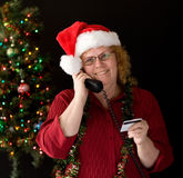 Shopping by phone. A grandma ordering holiday gifts over phone Stock Photos