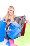 Shopping: Pretty Girl Pulls Shirt Out Of Shopping Bag Royalty Free Stock Photo