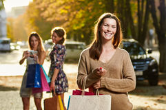 Shopping pretty woman portrait. Happy shopping women with a group of friends at the background Stock Photos
